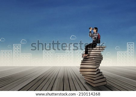 Female student sitting on the stack of books while looking for future by using binoculars - stock photo