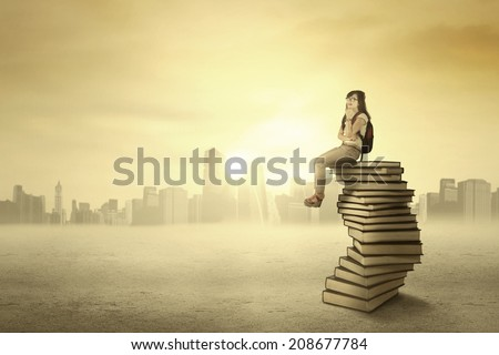 Female student sitting on the stack of books while thinking her future - stock photo