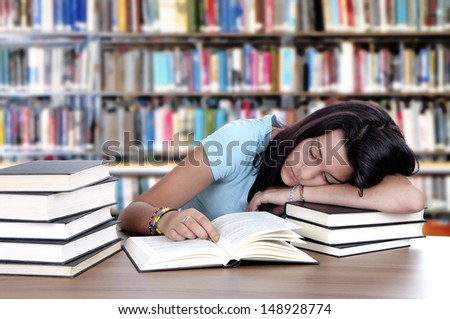 female student sleeping in a university library - stock photo