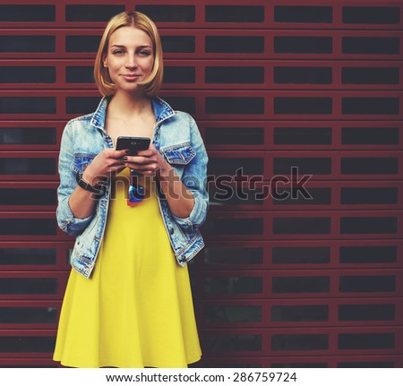 Female student smiling to the camera with smart phone in the hands, attractive hipster girl with mobile phone against blank copy space bright background for content or text message, chatting telephone - stock photo
