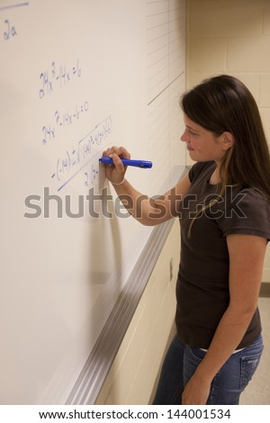 Female student solving an Algebra equation on a whiteboard. - stock photo