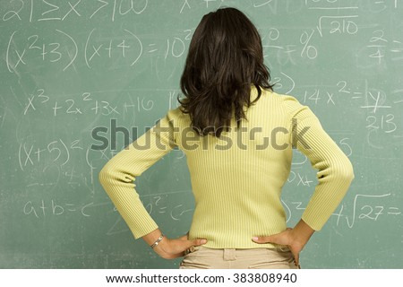 Female student stood in front of blackboard - stock photo