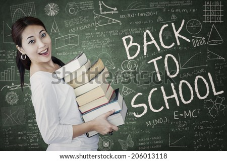 Female student studying at classroom while holding the source on book - stock photo