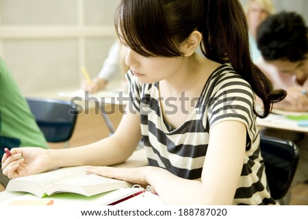 female student studying in classroom - stock photo