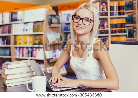 Female student studying on laptop in a library - stock photo