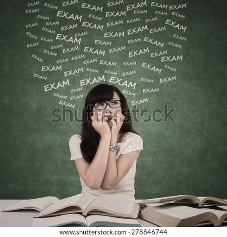 Female student studying to prepare exam and looks nervous by bite her nail - stock photo