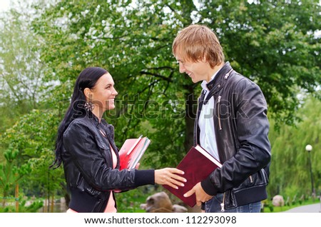 Female student talking with friend outdoors - stock photo