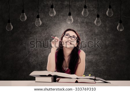 Female student thinking of ideas while sitting in the classroom - stock photo