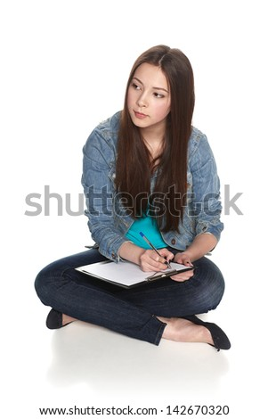 Female student thinking sitting on the floor in full length, looking to the side, isolated on white background - stock photo