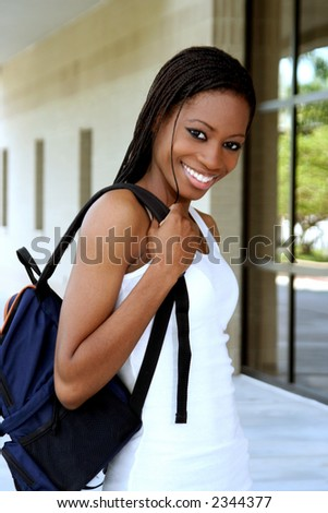 Female student walking on campus with a backpack - stock photo