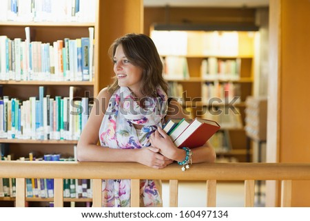 Female student with books looking to her side in the library - stock photo
