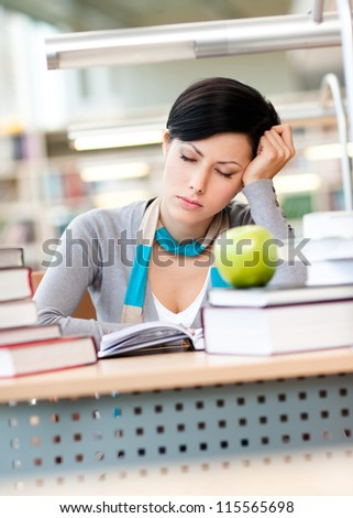 Female student with green apple sleeps sitting at the desk at the reading hall of the library. Data concept