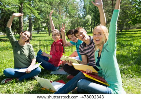 Female student with her friends studying together outdoors