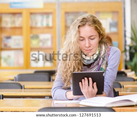 female student with tablet computer in library