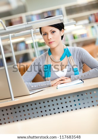 Female student working on the silver laptop sitting at the desk at the library