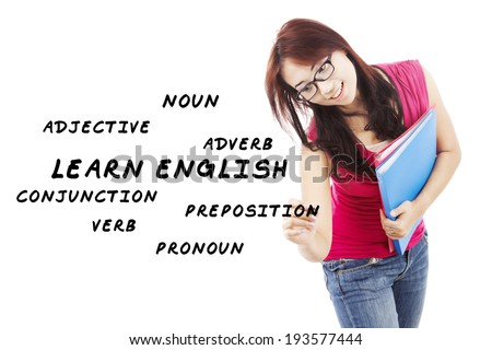 Female student writes english language materials on whiteboard - stock photo
