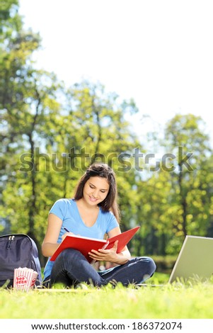 Female student writing in a notebook in park