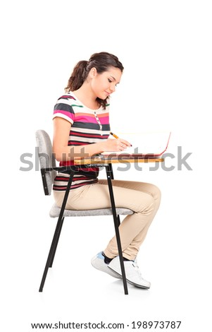 Female student writing in a notebook seated on a school desk isolated on white background