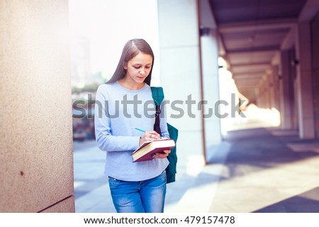 Female student writing notes in notepad