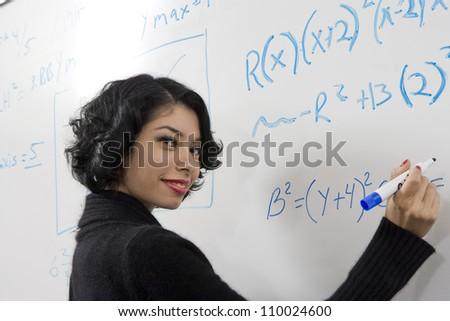 Female student writing on whiteboard - stock photo