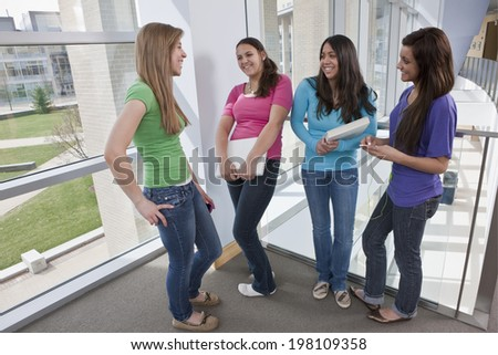 Female students gathered in a modern college building hall to talk