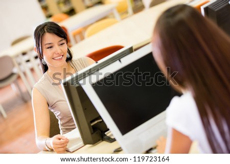 Female students researching on a computer at the library - stock photo