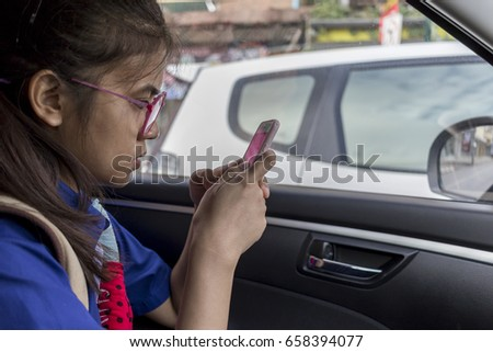Female students wear glasses good play mobile in the car on the road as traffic jams in the morning.