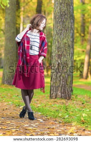Female Style Concept: Caucasian Brunette Woman Posing in Autumn Forest Outdoors.Vertical Image - stock photo
