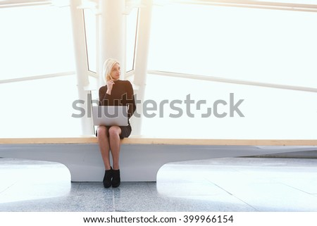 Female successful freelancer having mobile phone conversation during work on laptop computer in weekend in China. Modern woman is calling via cell telephone, while is sitting with net-book in office  - stock photo