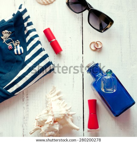 Female summer accessories (red lipstick, nail polish, sunglasses, jewelry) and striped top, with seashells. Marine style fashion, vacation and beach holiday, shopping and skin sun protection concepts. - stock photo