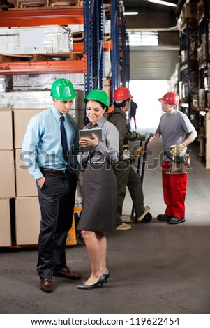 Female supervisor and male colleague using digital tablet with foremen communicating at warehouse - stock photo