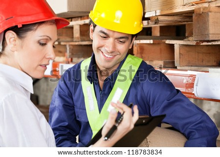 Female supervisor showing clipboard to young foreman at warehouse - stock photo