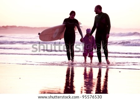 Female surfer and her familly walking in the beach at the sunset - stock photo