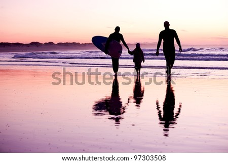Female surfer and her familly walking in the beach at the sunset