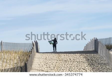 Female surfer at top of dune looking toward the ocean. - stock photo
