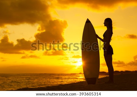 Female surfer looking out into the sunset.  - stock photo