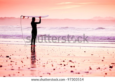 Female surfer on the beach at the sunset - stock photo