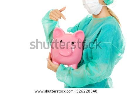Female surgeon doctor holding piggy bank. - stock photo