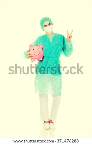 Female surgeon doctor with piggy bank shows victory sign - stock photo