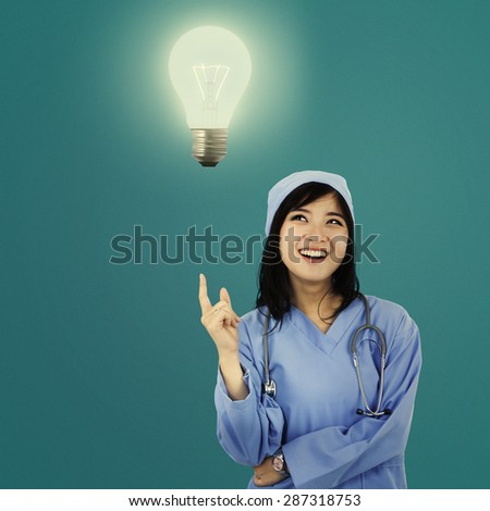 Female surgeon getting an idea and pointing at a bright light bulb