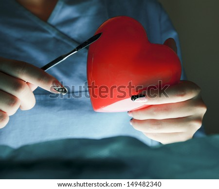 Female surgeon performing an operation on a heart patient - stock photo