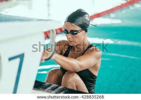 Female swimmer finished race. Climbing on swimming starting box - stock photo