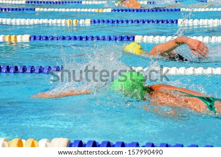 Female swimmers in a tight freestyle race - stock photo