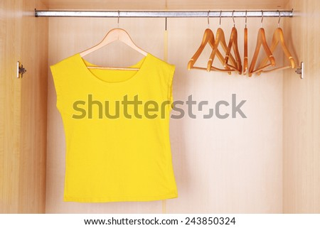 Female T-shirt with hangers in wardrobe - stock photo