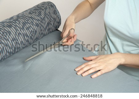 Female tailor cuts with scissors bolt of dark blue cloth - stock photo
