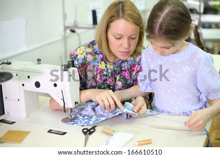 Female tailor sits at table with sewing machine and teaches girl how work with fabric. Focus on woman. - stock photo