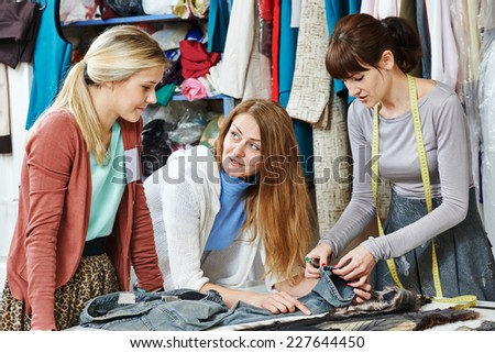 female tailor workers, modeller and stylist discussing clothing design in workshop - stock photo
