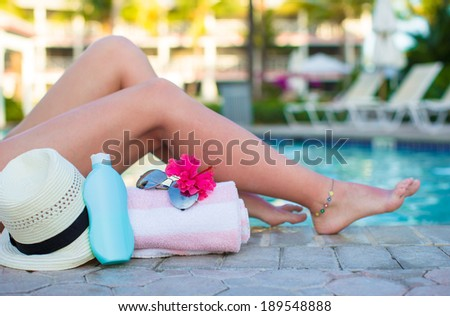 Female tanned legs near sun cream, hat, towel and sunglasses against the swimming pool - stock photo