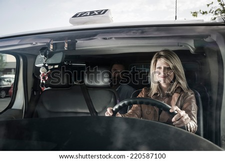 Female taxti driver with passenger - stock photo