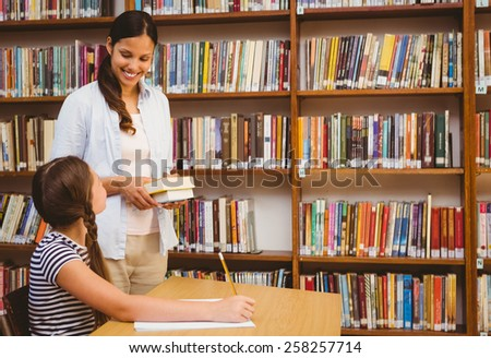 Female teacher and little girl reading book in the library - stock photo